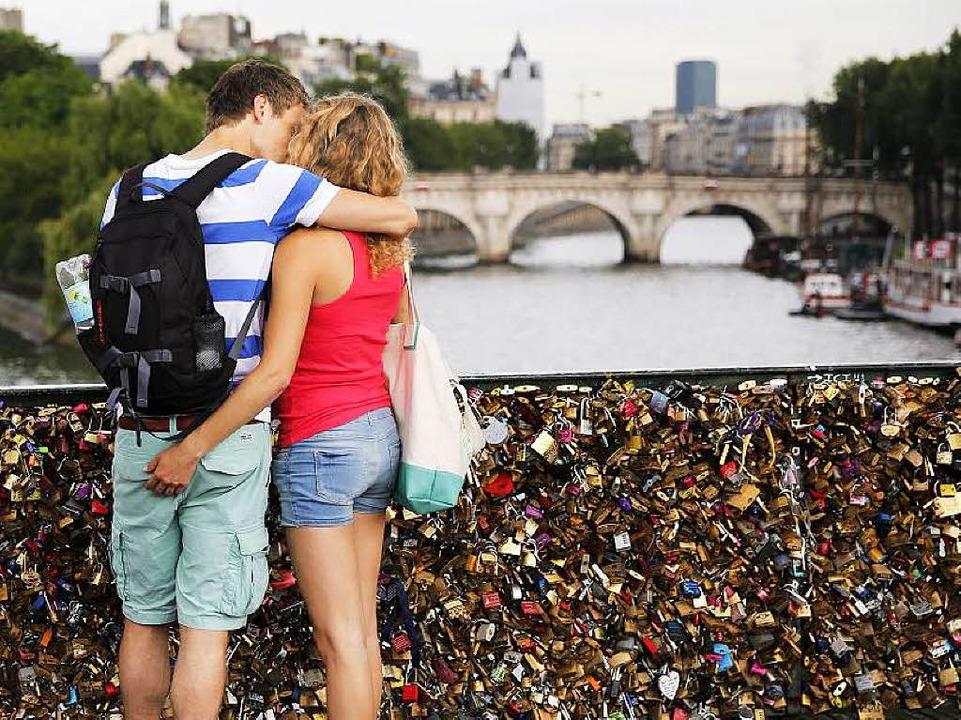 Ein Liebespaar auf dem vollbehängten Pont des Arts    Foto: dpa