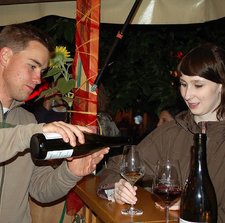 Matthias Willi half am Weinbrunnen aus...hle (stehend) im Gespräch mit Gästen.   | Foto: Fotos: Röderer/Weizenecker