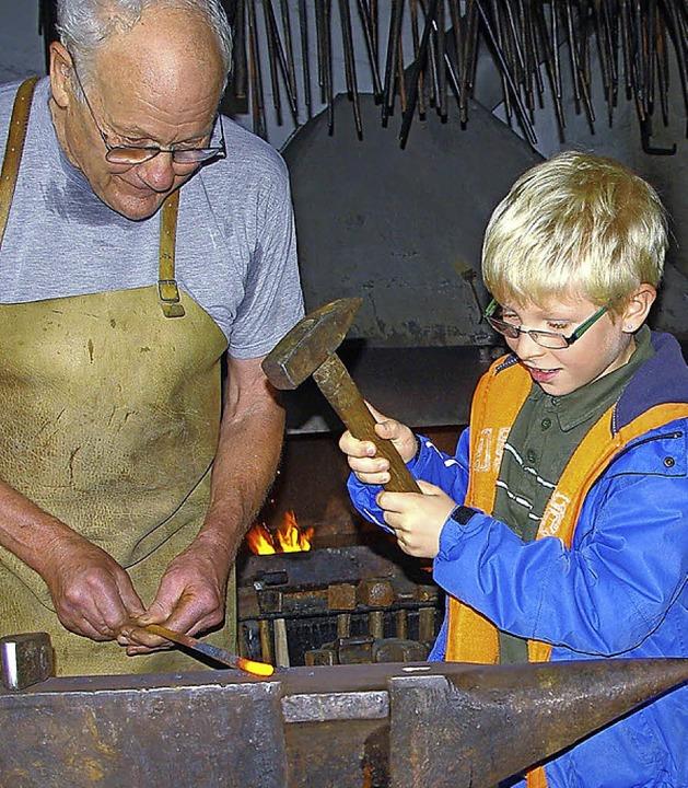 Franz Schütterer läßt Luk probieren, wie schwer es ist, Eisen zu bearbeiten  | Foto: Rolf Reißmann