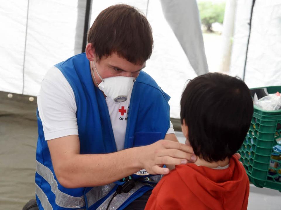 Eine Mitarbeiter des Roten Kreuz untersucht ein Kind von Flüchtlingen.  | Foto: dpa