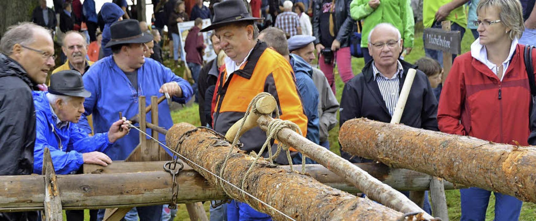 Männer bohren mit purer Muskelkraft Löcher in Holzstämme.  | Foto: Edgar Steinfelder