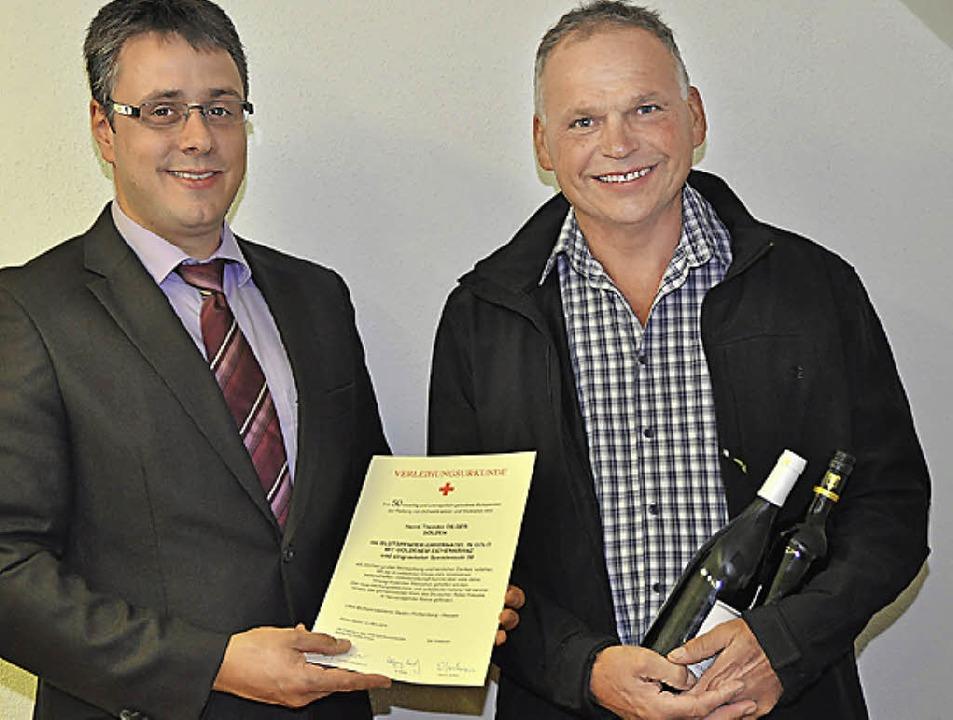 Markus Rees (links) ehrte Blutspender ...Dilger gleich mit zwei Flaschen Wein.     Foto: Steckmeister