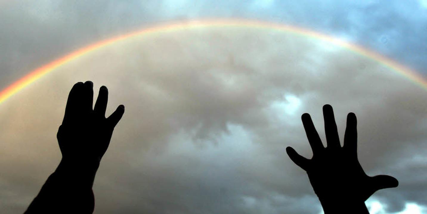 Wir fangen den Regenbogen: Zwei Kinderhände greifen zum Himmel hinauf.   | Foto: dpa