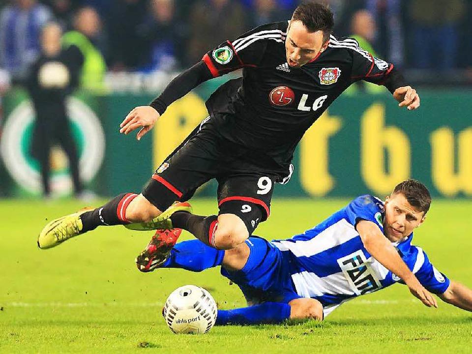 Der Magdeburger Niklas Brandt (rechts) attackiert Leverkusens Josip Drmic.    Foto: dpa