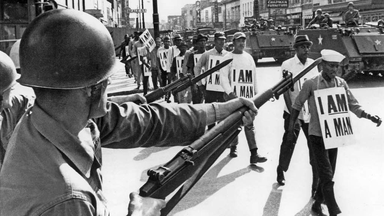 Gegen den Rassismus: Afroamerikaner fo...onalgarde beschützt ihren Protestzug.   | Foto: dpa