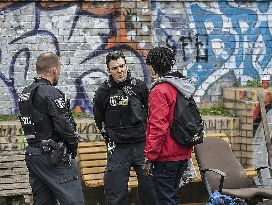 Polizisten kontrollieren  im Görlitzer Park einen Mann.   | Foto: dpa