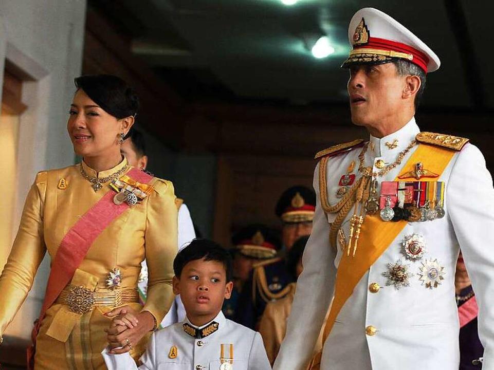 Prinz Maha Vajiralongkorn m it seiner Frau Srirasm und ihrem Kind   | Foto: AFP