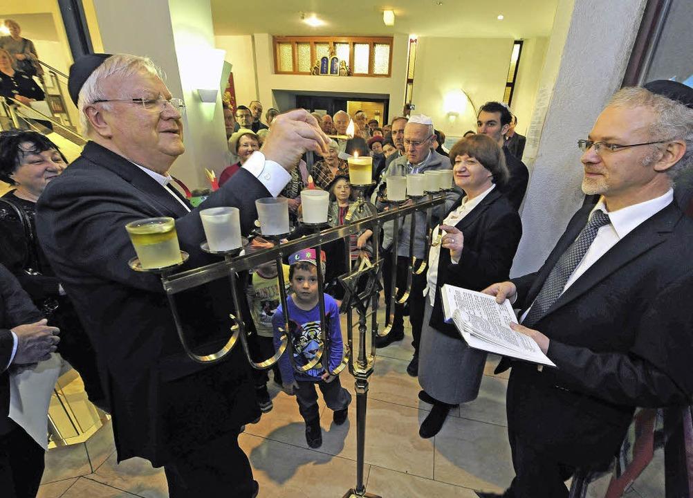 Wolfgang Gaber zündet die erste Chanuk...an – rechts Rabbiner Pavlovsky.   | Foto: Thomas Kunz