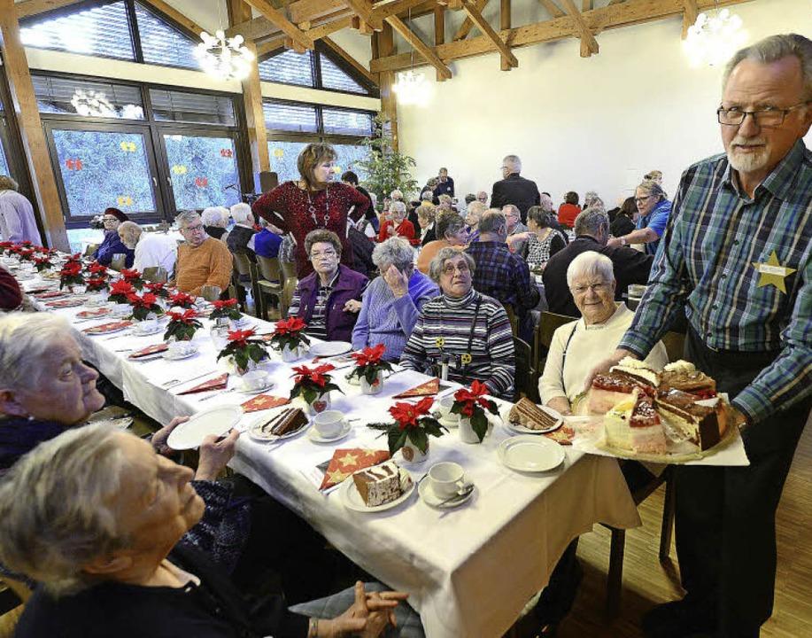 Der ehrenamtliche Helfer Emil Pfistner (rechts) teilt Kaffee und Kuchen aus.   | Foto: ingo schneider