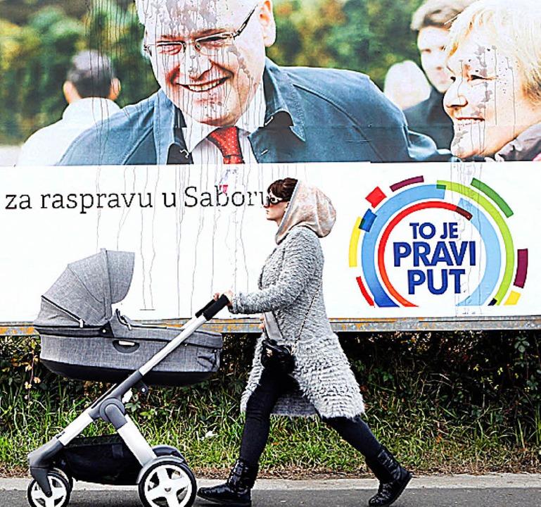 Eine Frau geht an einem Plakat von Präsident Josipovic vorbei.   | Foto: DPA