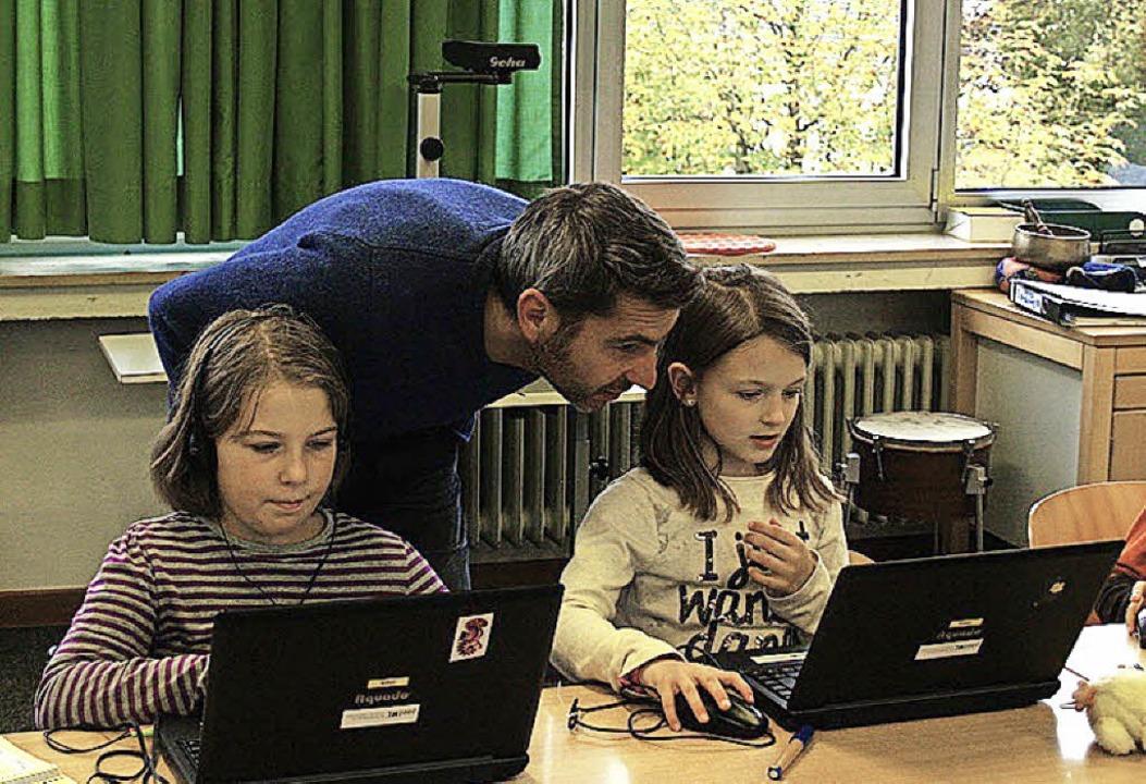 Rektor und Mathematiklehrer Reinhard B...r Klassen 3/4 Matheaufgaben am Laptop.  | Foto: Hönes/LMZ