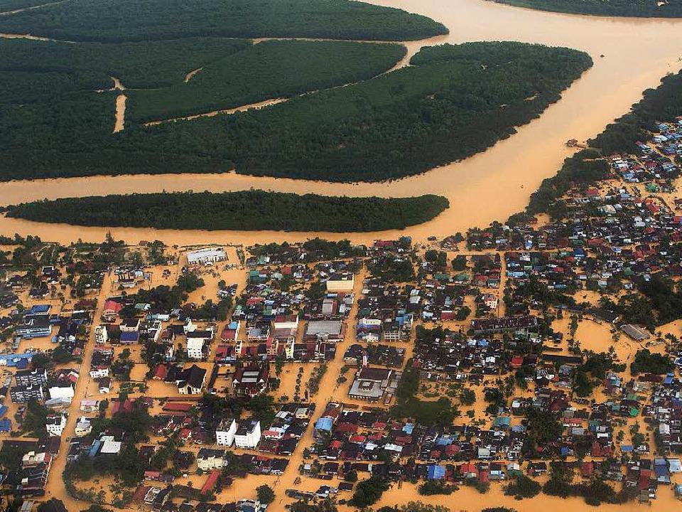 Schlammbraune Wassermassen überfluten in Malaysia  ganze Dörfer.  | Foto: AFP