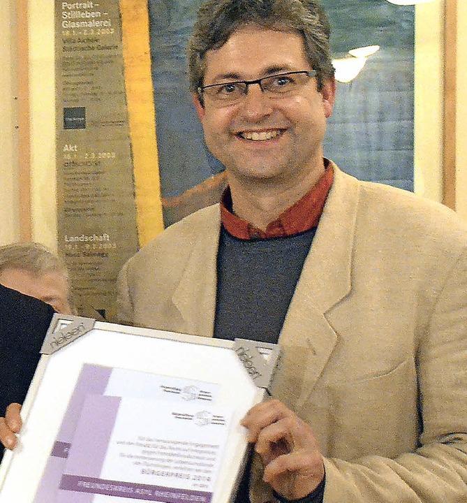 Jörg Hinderer reicht die Bürgerpreisurkunde an die Gruppe weiter.  | Foto: Ingrid Böhm-Jacob