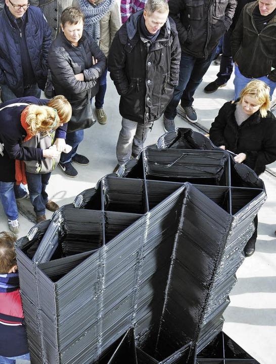 Besucher nehmen ein Bauteil in Wabenform unter die Lupe.  | Foto: dpa