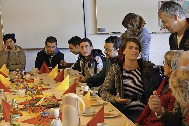 Helfer und Flüchtlinge an einem Tisch