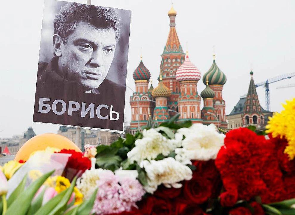 Mit Blumen gedenken viele Russen der E...r St. Basilius Kathedrale beim Kreml.   | Foto: DPA