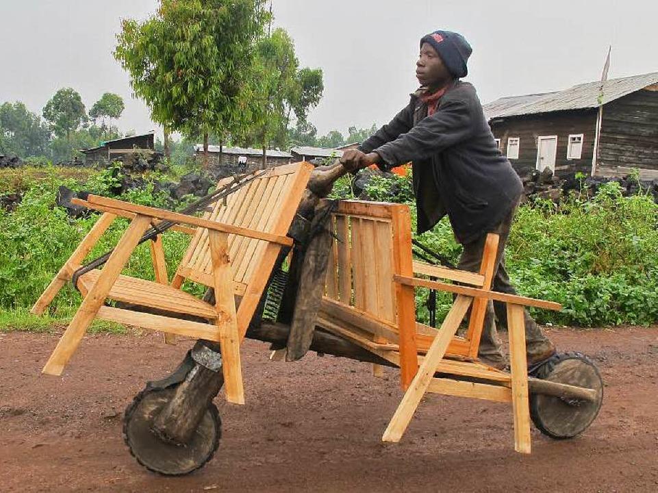 David Bisore transportiert zwei Bänke ... Kongo beliebten  Chikudu-Tretrollern.  | Foto: Dieterich