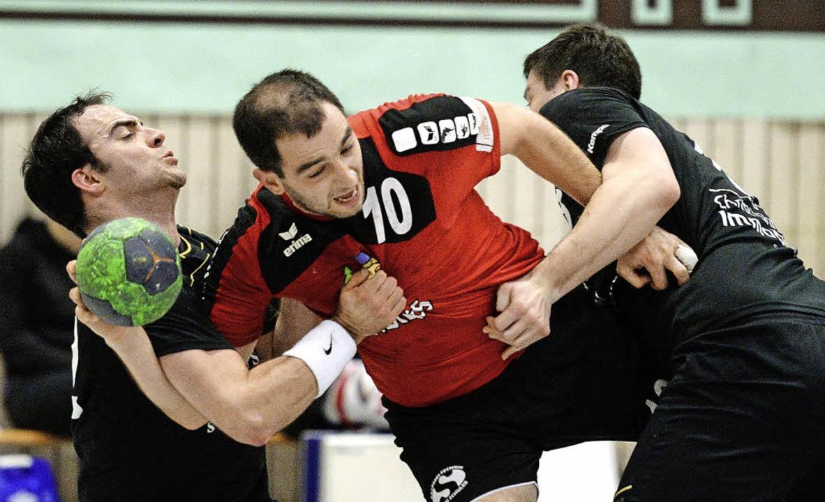 TuS-Handballer Clément Martinez hängt ...r mit  Sebastian Preißl (links) fest.     Foto: Seeger