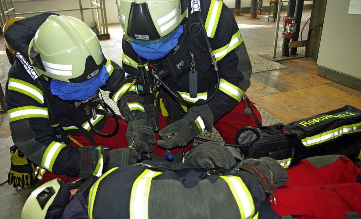 Mit verdecktem Visier am Helm tasteten...uft an die Maske des Verunglückten an.    Foto: Rolf Reißmann