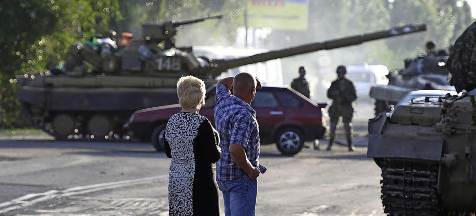 Ein Paar  beobachtet, wie  Panzer der ...ie Waffen schweigen bis heute  nicht.   | Foto: AFP