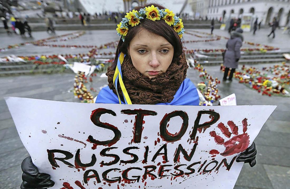 Eine ukrainische Frau protestiert Ende...uerfeier für die Opfer von  Mariupol.   | Foto: dpa