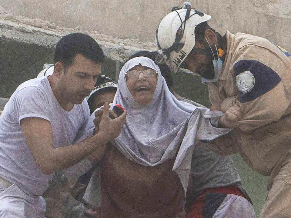 Nach einem Angriff mit Fassbomben in A...en  Helfer diese Frau in Sicherheit.    | Foto: AFP