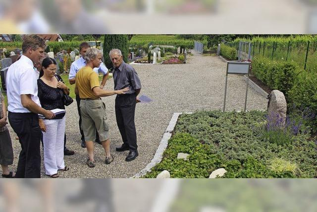 Gärtner pflegen Gräberfeld auf Friedhof