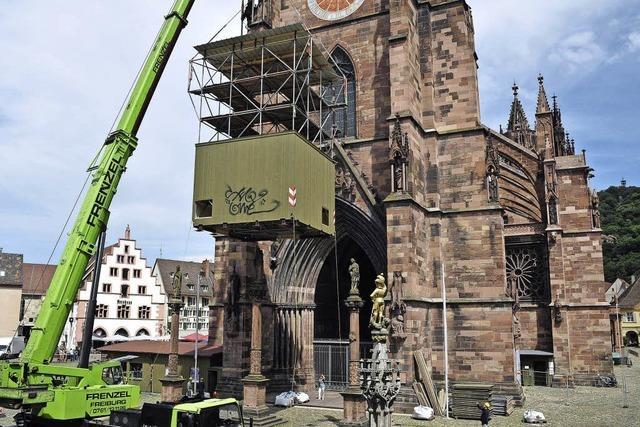 Ein Kranwagen verschiebt ein Baugerüst vor dem Freiburger Münster