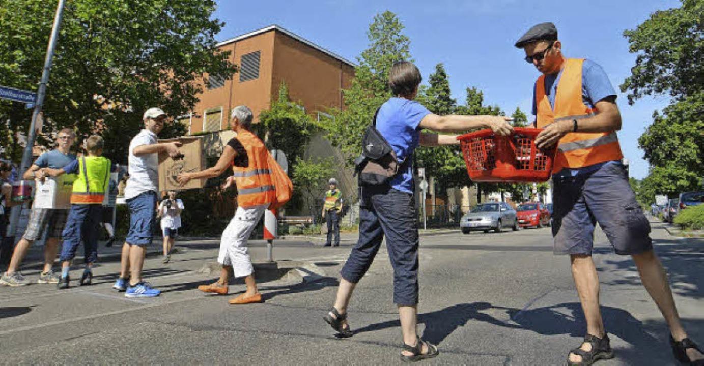 Eine Menschenkette lässt Pakete und Kö...Da müssen Autofahrer schon mal warten.  | Foto: Barbara  Ruda