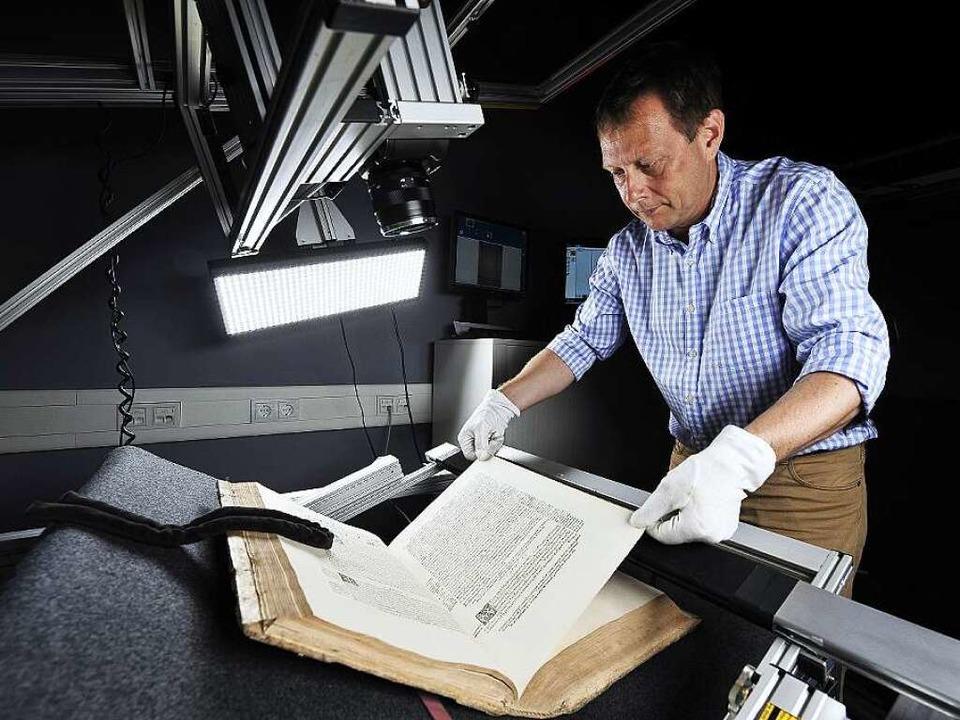 Mit viel Gefühl: Oliver Rau, Leiter de...tografieren eines historischen Buches     Foto: Fotos: Thomas Kunz/Uni Freiburg