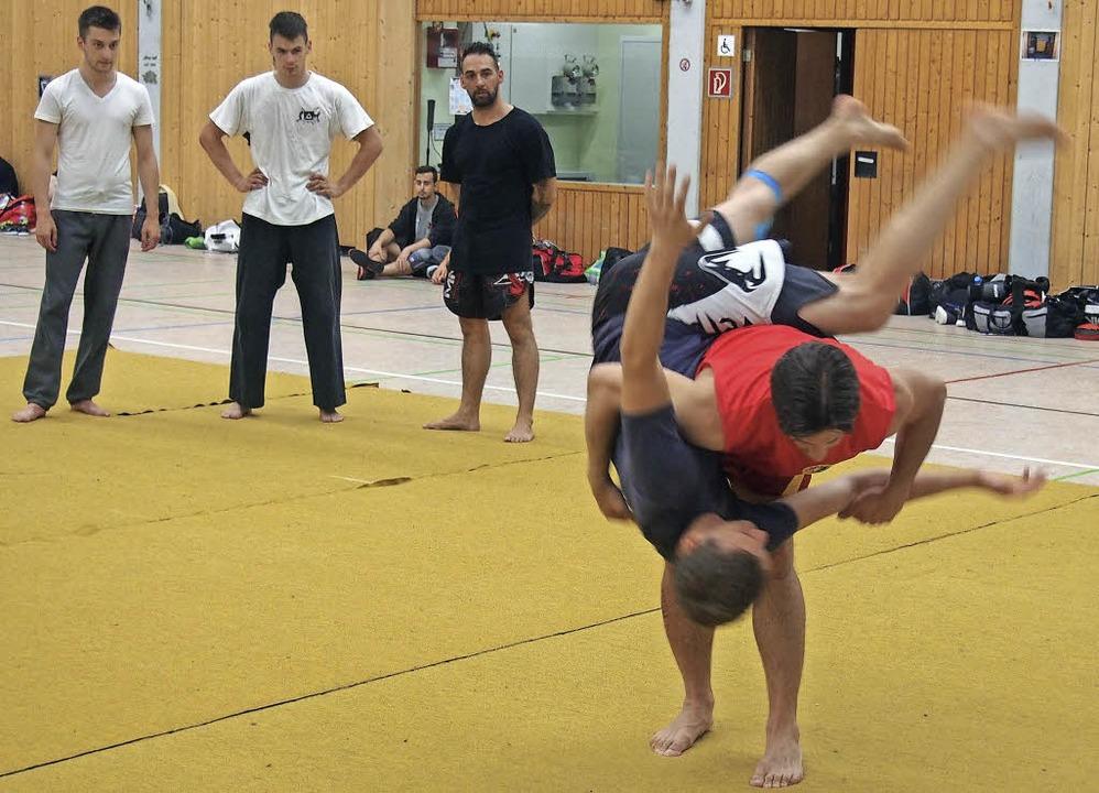 Der Trainer und erfolgreiche Kampfspor...hmern mit einem Partner Wurftechniken.    Foto: Katharina Schiller