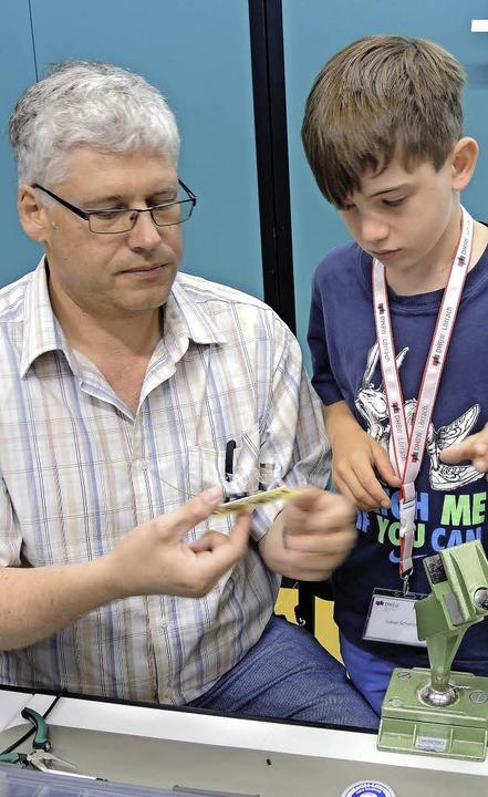 Edgar Laile überprüft die Platine, auf...) elektronische Bauteile gelötet hat.     Foto: ZVG