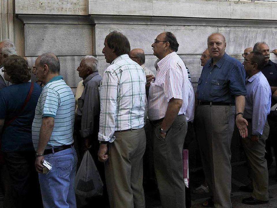 Griechen stehen im Juli Schlange vor einer Bank in Athen.    Foto: dpa