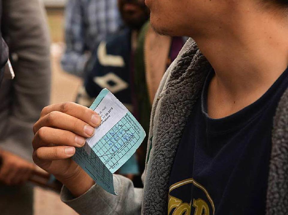 Ein Flüchtling in Trier mit seiner Essenskarte   | Foto: DPA