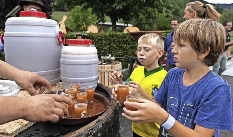 Kinder verteilten frisch gepressten Apfelmost an die Besucher.  | Foto: Photographer: Gabriele Zahn