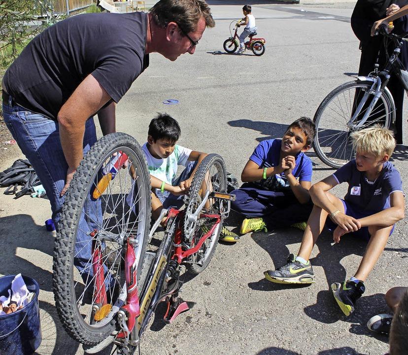 Markus Schwarz erklärt den Kindern, wie man ein Fahrrad auch  richtig pflegt.  | Foto: Reinhard Cremer