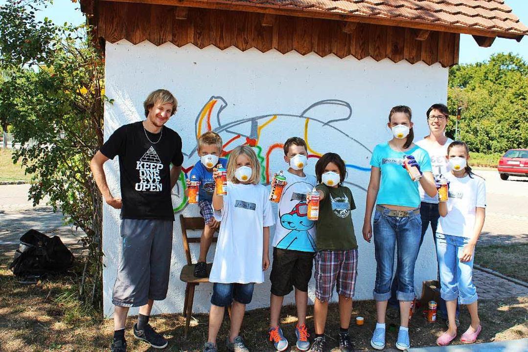 Janik mit den Kindern der Graffitiakti...tenheimer Ferienprogamms am Waaghäusle  | Foto: Mario Schöneberg