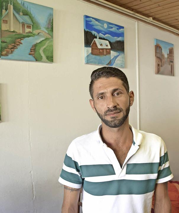 Saif Ali lebt seit knapp einem Jahr in...e, hinter ihm von ihm gemalte Bilder.   | Foto: Herwig Popken