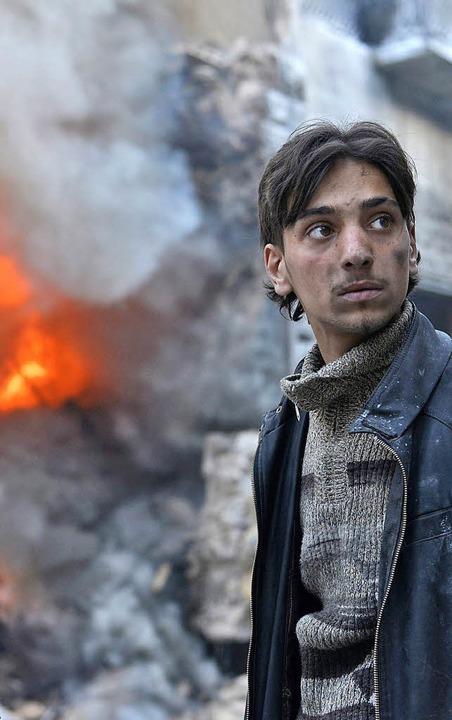 Syrer vor den Trümmern eines brennenden Hauses     Foto: DPA