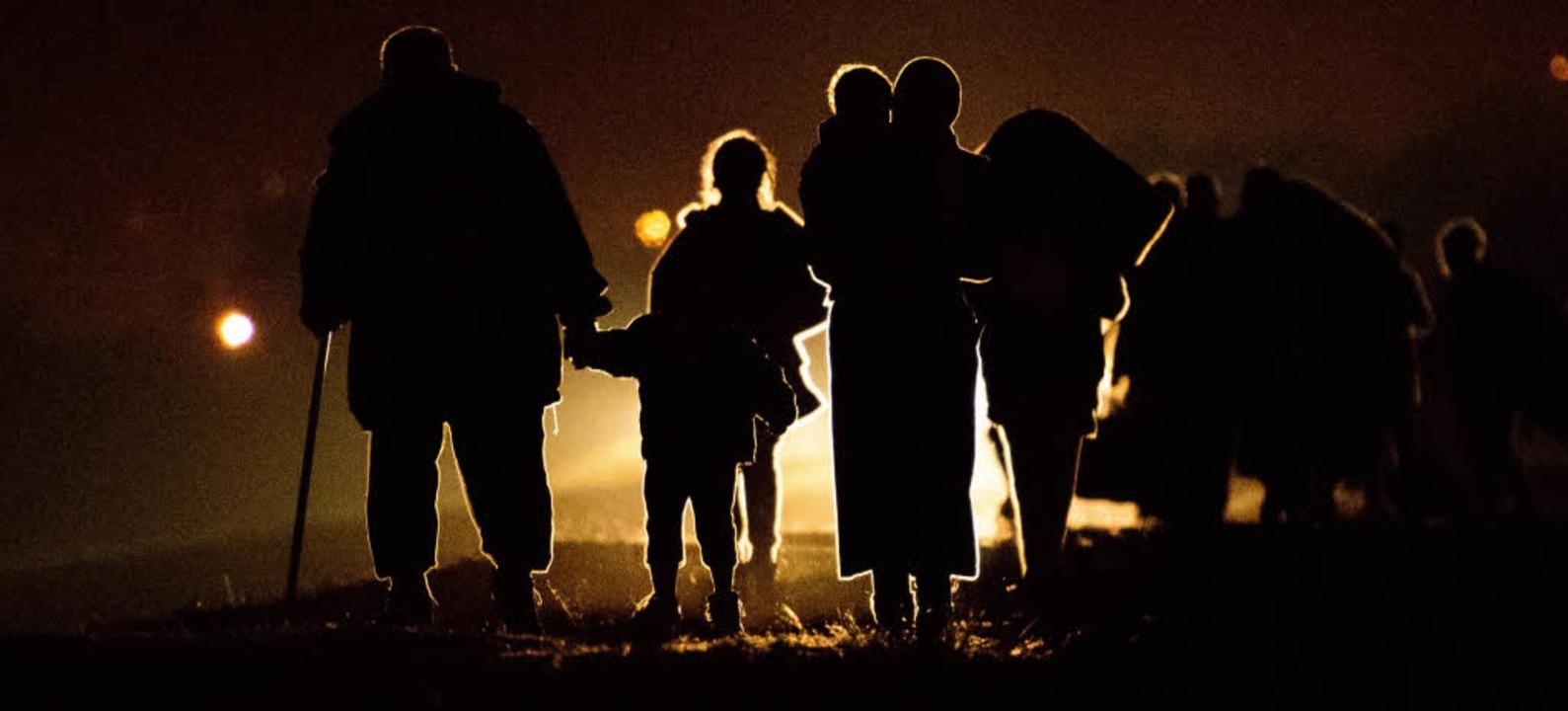 Flüchtlingsfamilien laufen im Dunkeln auf das Camp Brezice zu.    Foto: AFP