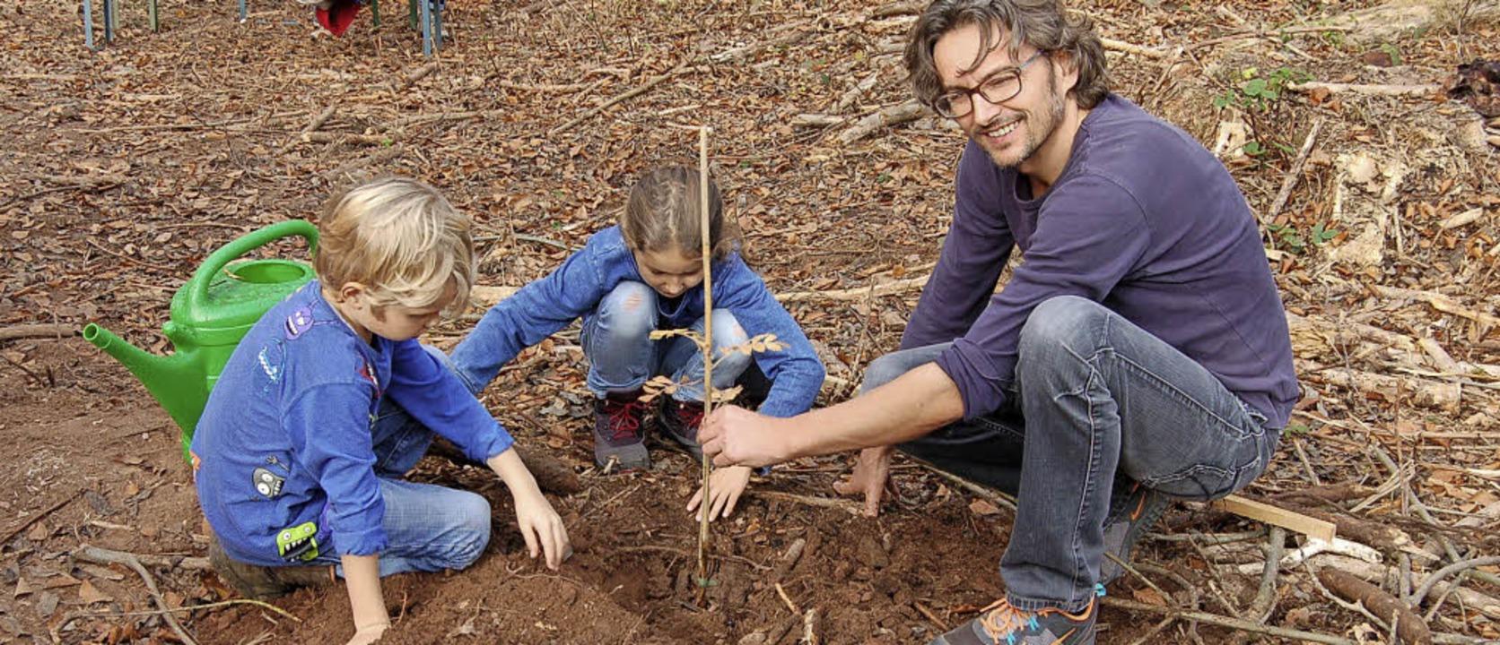 Alexander Nold mit seinen beiden Kindern Emmi und Milan setzen einen Speierling  | Foto: Christian Ringwald