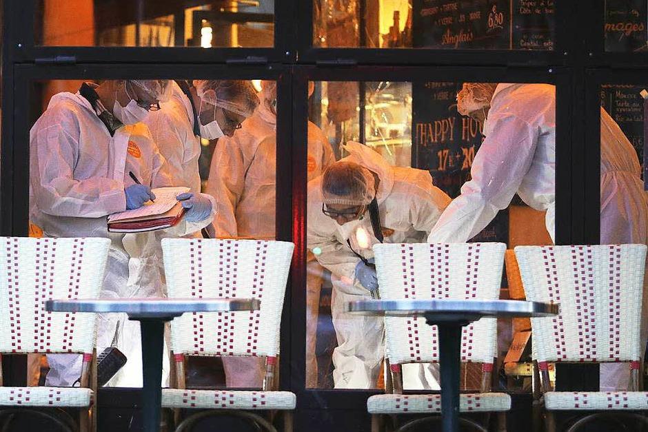 Kriminaltechniker untersuchen den Tatort im Café Bonne Biere. (Foto: AFP)