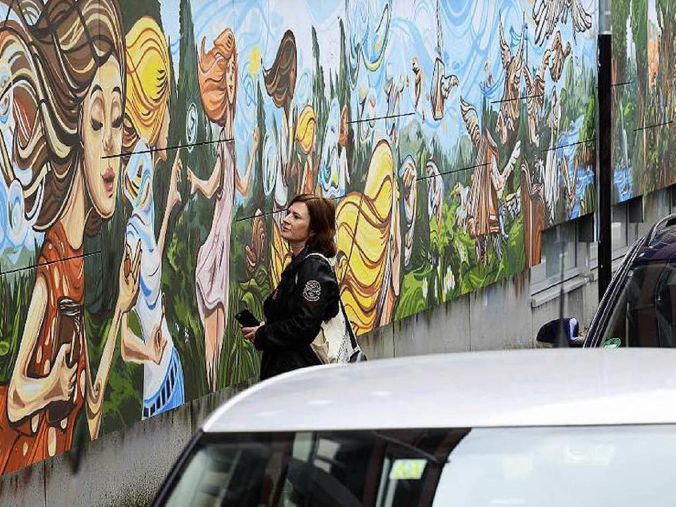 Eine Passantin bewundert einen kleinen...r langen Kunstwerks in der Rosastraße.  | Foto: I. Schneider