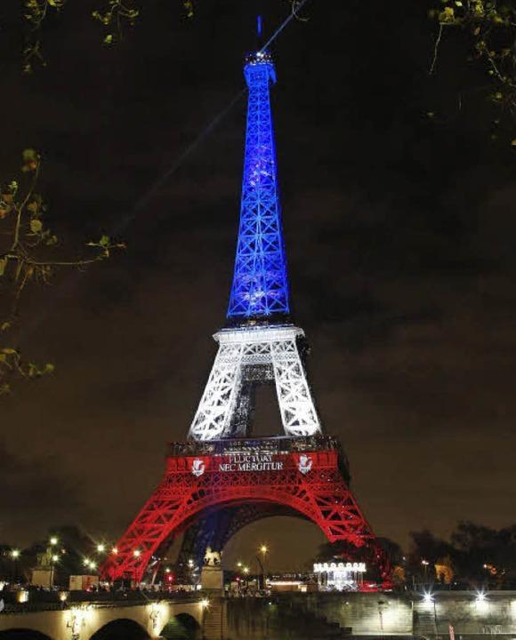 In Blau-Weiß-Rot: Der Eiffelturm steht...s für die Wehrhaftigkeit Frankreichs.     Foto: dpa/AFP