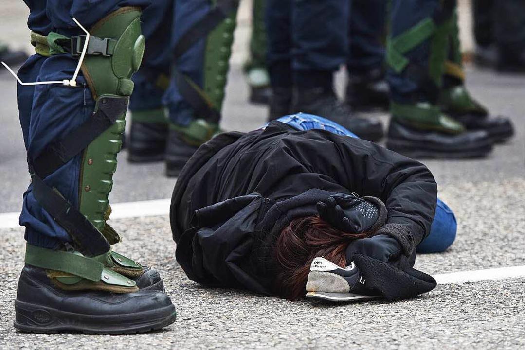 Eine Gegendemonstrantin liegt  in Wein...gs neben Polizeikräften auf dem Boden.    Foto: dpa
