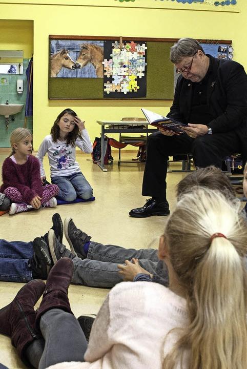 Richard Leibinger liest in der Grundsc...chholz vor einer Gruppe Erstklässler.   | Foto: Fotos: Zahn
