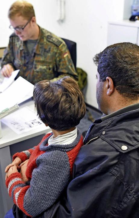 Ein Soldat stellt in Heidelberg Formul...eine syrische Flüchtlingsfamilie aus.   | Foto: dpa