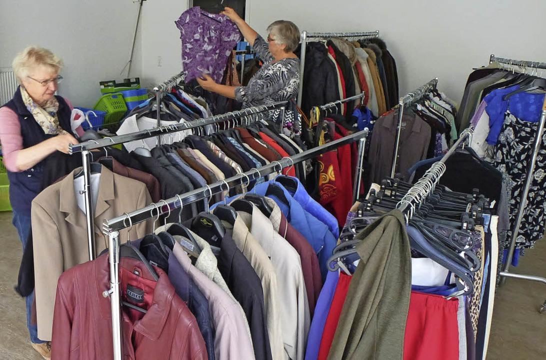 Zwei der Mitarbeitenden, Astrid Wenger...iten die Kleidung für den Verkauf vor.    Foto: Peter Stellmach