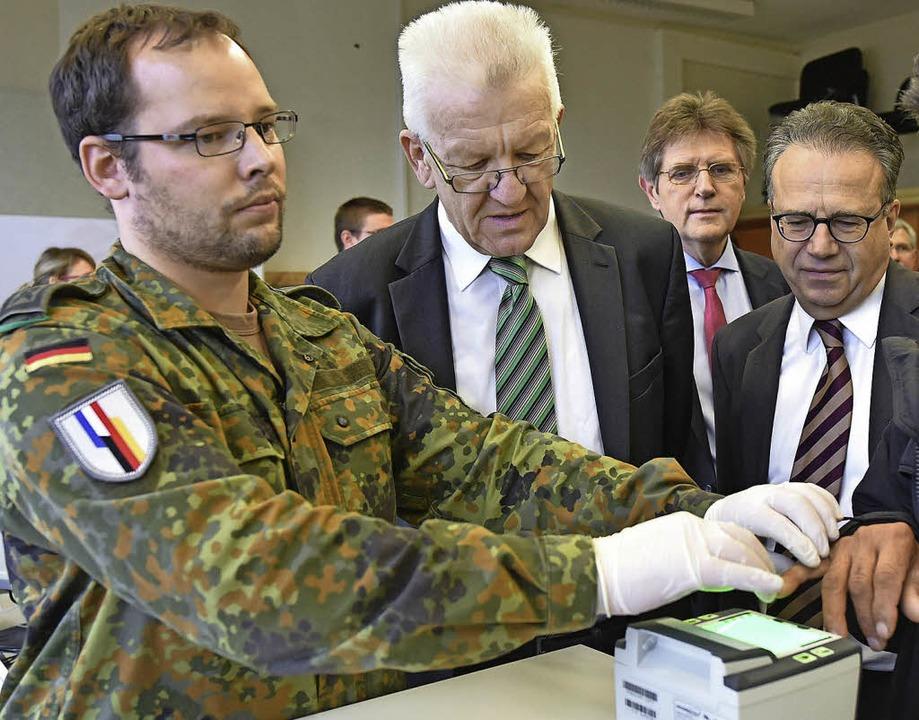 Amtschef  Weise (r.) und Politiker  Kretschmann (M.)  bei einer Registrierung   | Foto: dpa