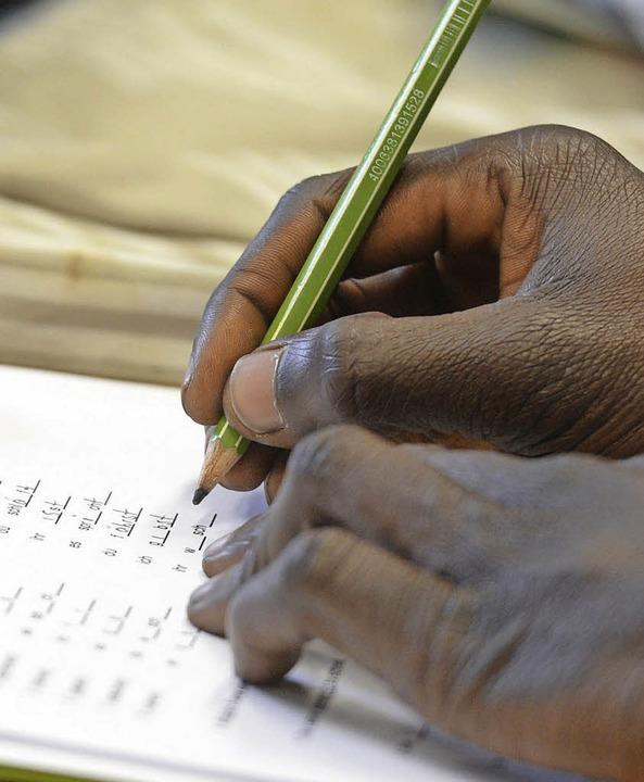Ein Schüler schreibt im Deutschunterricht für Asylbewerber auf ein Arbeitsblatt.  | Foto: dpa